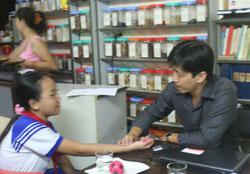 Lương y Vũ Trọng Vĩnh đang bắt mạch cho một bệnh nhân
